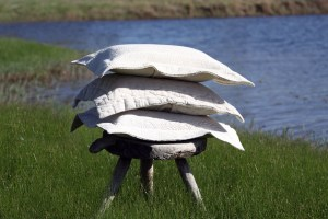 A stack of pillows in shams sit on an old three legged stool in the grass by the edge of a pond